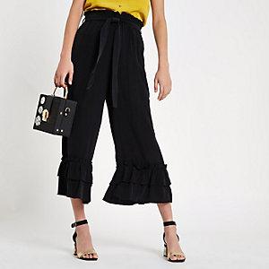Jupe-culotte en soie noire à volants nouée à la taille
