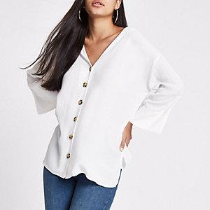 Witte blouse met knoopsluiting voor en band op de rug