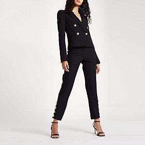 Zwarte smaltoelopende broek met knopen aan de zoom