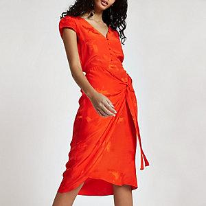 Robe mi-longue rouge boutonnée et nouée sur le devant