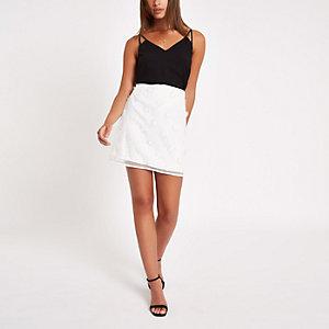 Mini-jupe à fleurs blanche ornée