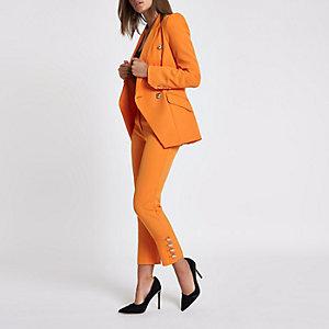 Oranje smaltoelopende broek met goudkleurige knopen