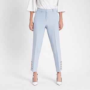 Lichtblauwe smaltoelopende broek met knopen aan de zoom