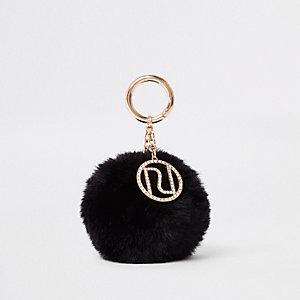 Zwarte sleutelhanger met RI-logo en pompon van imitatiebont