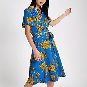 Robe mi-longue bleu à fleurs nouée sur le devant
