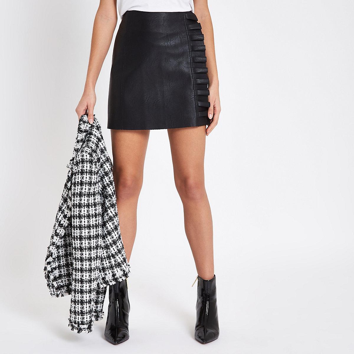 Mini-jupe en cuir synthétique noire à volant sur le côté