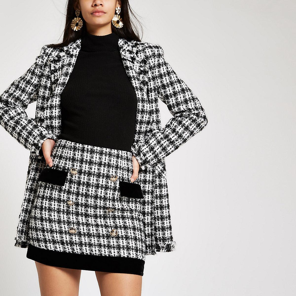 Mini-jupe en maille bouclée noire bordée de velours