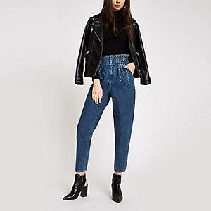 Blaue, nietenverzierte Jeans