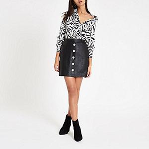 Mini-jupe en cuir synthétique noire boutonnée