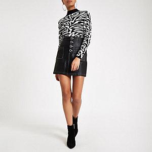 Mini-jupe en cuir synthétique noire avec poches devant