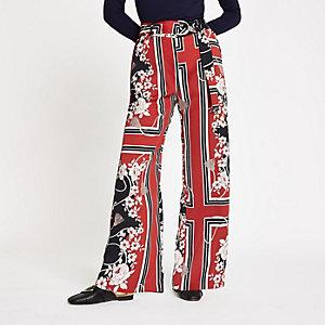 Rode gebloemde broek met wijde pijpen en ceintuur met D-ring
