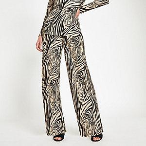 Hose in Creme mit weitem Beinschnitt und Zebra-Print