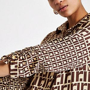 Bruine blouse met ruches op de mouwen en RI-logo