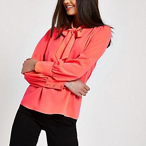 Neonroze ruimvallende blouse met strik bij de hals