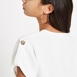 Wit T-shirt met V-hals en knopen op de schouder