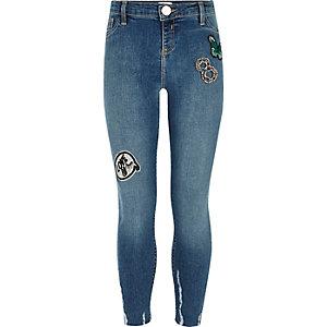 Jean skinny bleu avec écussons et ourlets usés pour fille