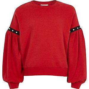 Roter Pullover mit Puffärmeln