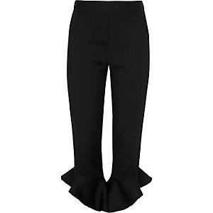 Girls black asymmetric frill hem trousers