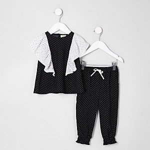 Outfit mit schwarzem, gepunktetem Oberteil mit Rüschen