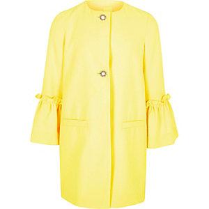 Gele jas met ruches aan de mouwen en parelknopen voor meisjes