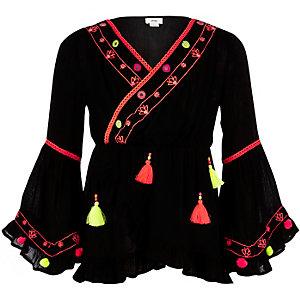 Zwarte tuniek met pompons en ruches aan de zoom voor meisjes