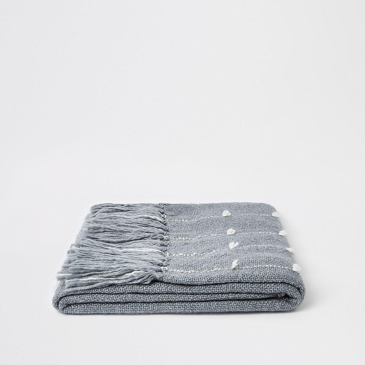 Couverture grise avec fils cousus